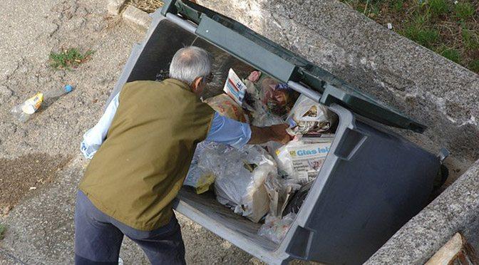 man digging in trashcan